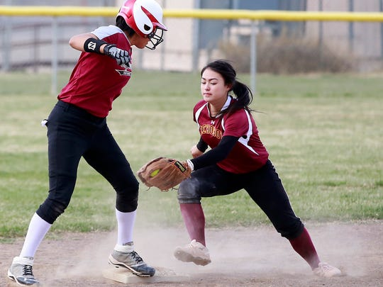Rehoboth Christian's Tyra West tries to tag Shiprock's Adarra Jim at second base during their game on Tuesday at Shiprock High School in Shiprock.