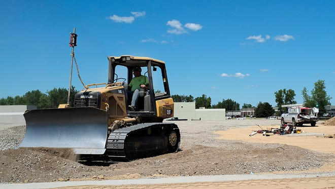 A bulldozer moves some gravel around at the site of a new 50,000 square foot TFT Global plant located on Empire Way in Delta Township on Monday.