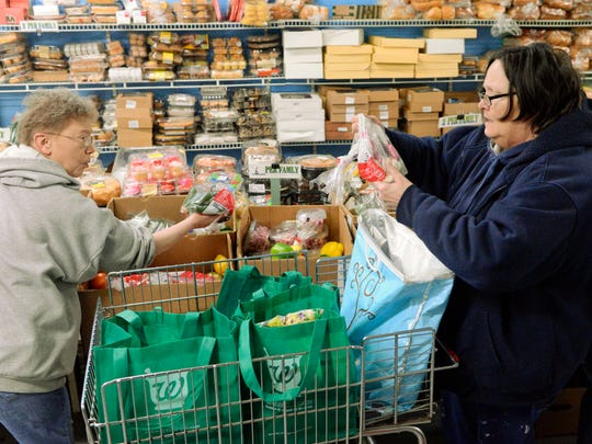 Recipient Terri Boast, right, selects a bag of garlic as volunteer Rose Mayer asks her if she would like a bag of peppers Tuesday at Peter's Pantry in Manitowoc.
