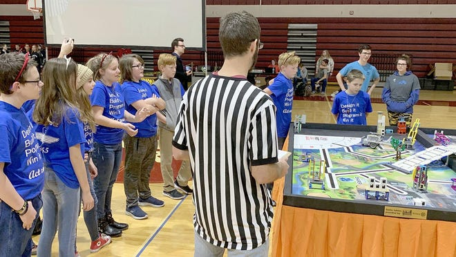 The Skyline LightningBotz surround a game table at the FIRST Lego League robotics tournament in Salina. The LightningBotz placed eleventh out of 23 teams at the tournament.