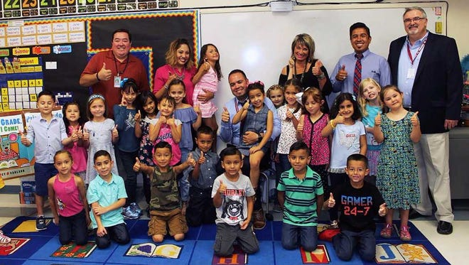 Superintendent Greg Ewing, far right, surprises a first-grade bilingual classroom at Central Elementary School on Monday, Aug. 14, 2017, the first day of classes. The students gave a thumbs-up in reaction to his visit. Others with the students were, from left, Deputy Superintendent Gabe Jacquez; classroom teacher Laura Bryant holding her daughter; Chief Officer of Equity, Innovation & Social Justice Roberto Lozano, holding his daughter; Assistant Superintendent of Learning Tiffany Gomez; and Central Elementary Principal Michael Chairez