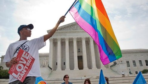 Carlos McKnight, 17, of Washington, holds up a flag in support of gay marriage outside of the Supreme Court in Washington, Friday June 26, 2015. A major opinion on gay marriage is among the remaining to be released before the term ends at the end of June.