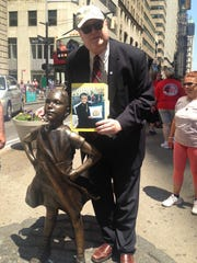 Columnist Jim Patterson stands next to the Fearless Girl statue in New York.
