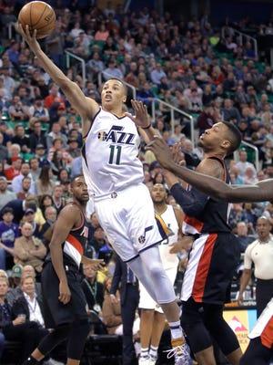 Utah Jazz guard Dante Exum (11) lays the ball up as Portland Trail Blazers guard Damian Lillard, right, defends during the second half in an NBA basketball game Tuesday, April 4, 2017, in Salt Lake City. The Jazz won 106-87. (AP Photo/Rick Bowmer)
