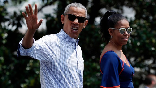 President Barack Obama waves and calls out to media as he and first lady Michelle Obama walk from the White House, Saturday, Aug. 6, 2016, in Washington, to board Marine One, with their daughters Sasha and Malia, en route to Andrews Air Force Base, Md., and on to Martha's Vineyard for a family vacation. (AP Photo/Carolyn Kaster)