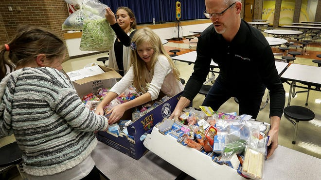 John Williamson, of Food Rescue, and students from Hinkle Creek Elementary in Noblesville sort food that was rescued from being thrown away by students during their lunch break. The rested food is then taken to area food pantries.