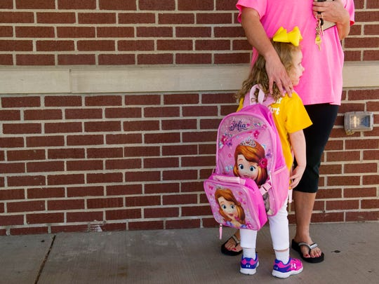 "Darra Eades, 4, waits with her mom, Tiffany Berrong, for the doors to open at the Thelma B. Johnson Early Learning Center on the first day of school Monday morning. ""This is her first day ever,"" mom said of the excited youngster. For older students, the first day of school in Henderson County was Aug. 10."