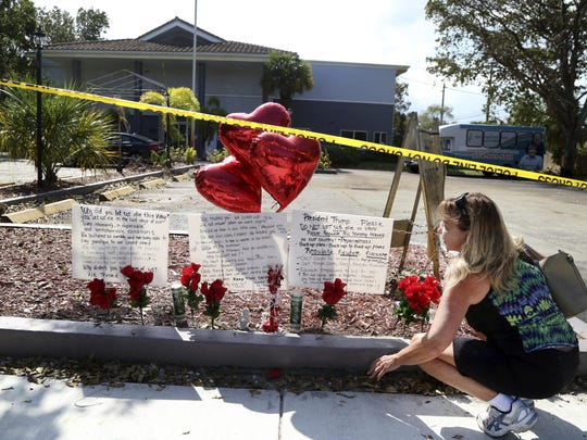 Janice Connelly of Hollywood sets up a makeshift memorial in memory of the senior citizens who died in the heat at The Rehabilitation Center at Hollywood Hills, Fla.