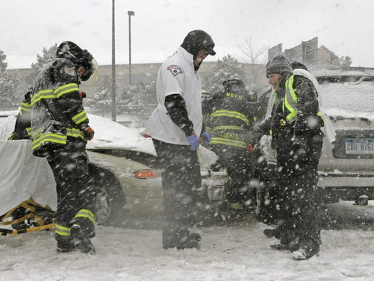 Rescue crews are pelted with snow at the scene of an