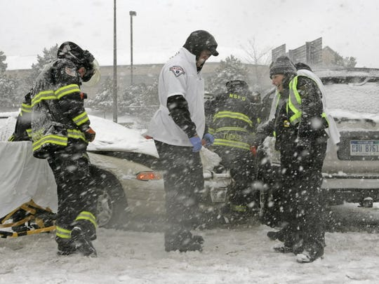 Rescue crews are pelted with snow at the scene of an accident on I-43 near Brown Deer Road on March 21, 2008, as more than a foot of snow was falling on the Milwaukee metro area.