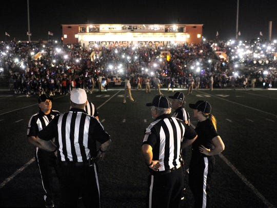 Game officials wait for the Shotwell Stadium lights