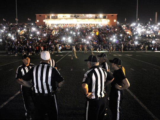 Game officials wait for the Shotwell Stadium lights to come back during the third quarter of Friday's crosstown football game between Abilene High and Cooper. Play resumed after about a 15-minute delay. Cooper won, 49-35.