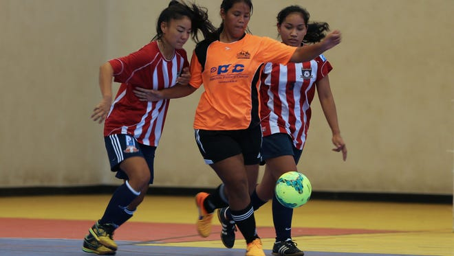 The Lady Crushers' Maria Abbey Iriarte stays in control of the ball as she makes her way closer to the goal ahead of the Lady Strykers' Kimberly Sherman (left) and Sheena Borja (right) during a Week 1 match of the Bud Light Women's Futsal League at the Guam Sports Complex Gym Sunday. The Lady Crushers defeated the Lady Strykers 4-2.