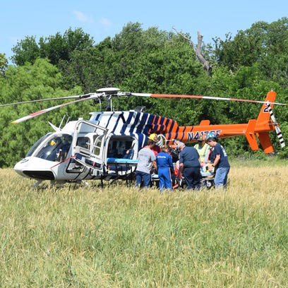 Medical personnel load a man into a helicopter after