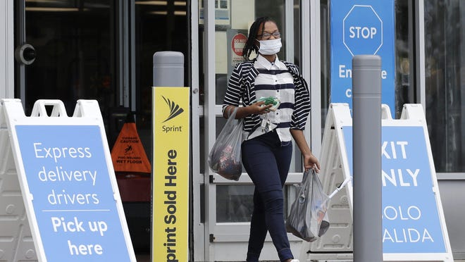 A shopper wears face masks as she leaves a Walmart retail store in Vernon Hills on July 30.