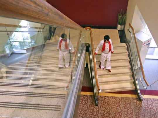 Lloyd Cornelius of Honea Path, dresses as Elvis from the 1970s, walks down the stairs toward the exit doors at Electric City ComiCon at the Anderson County Library in Anderson.