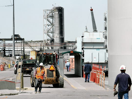 Workers are seen guiding vehicles on the main road earlier this year at the Four Corners Power Plant in Fruitland.