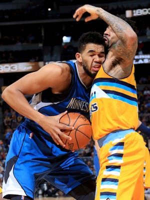 Minnesota Timberwolves center Karl-Anthony Towns (32) is fouled by Denver Nuggets forward Wilson Chandler (21) during the first half of an NBA basketball game Wednesday, Dec. 28, 2016, in Denver.
