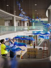 """Glass artist Craig Mitchell Smith, right, hangs his installation entitled """"Lifted"""" with the assistance of Ben Freeman in the lobby of Sparrow's Herbert-Herman Cancer Center."""