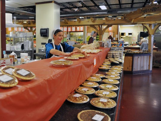 Sylvia Beiler lays out pies Thursday at one of the display cases in the Amish Market, which occupies most of the lower level of the Landis MarketPlace in Vineland.