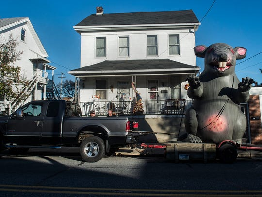 An inflatable rat on a flatbed truck is parked outside