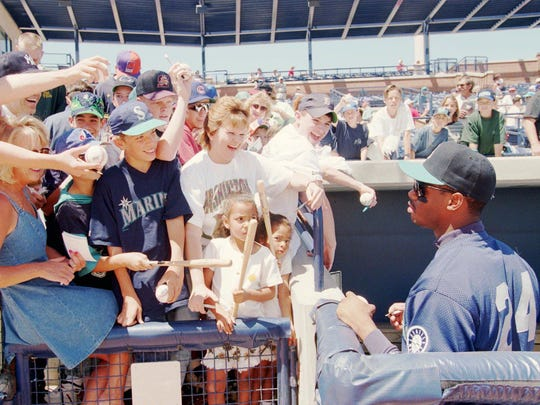 Ken Griffey Jr. is besieged by autograph seekers prior to a Mariners Cactus League game in 1995.