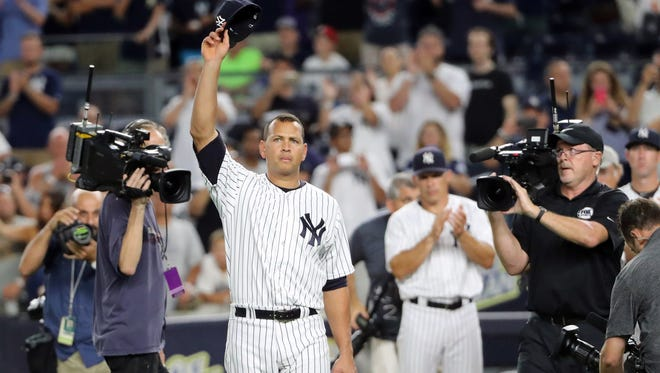 Alex Rodriguez tips his cap in a farewell gesture to the fans.
