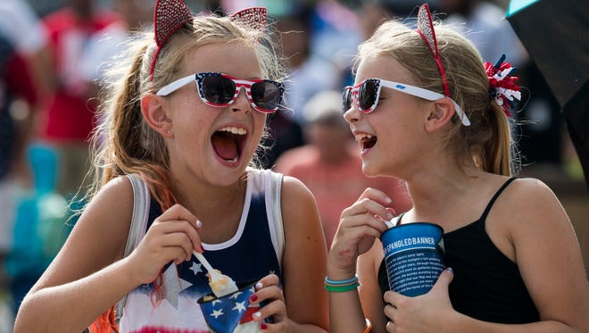 From left, Kaylin Zelenak, 8, and Audrina Ische, 9, share a few laughs while enjoying the festivities at the Red White and Boom Fourth of July event in Cape Coral, Wednesday afternoon.