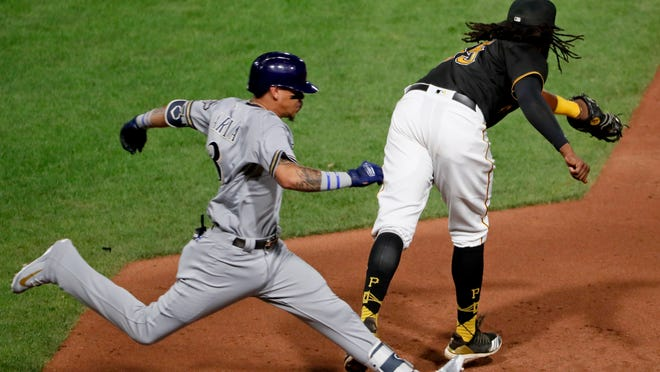 Milwaukee Brewers' Orlando Arcia, left, beats out a bunt for a hit as Pittsburgh Pirates first baseman Josh Bell is pulled off the bag in the fifth inning of a baseball game, Friday, Sept. 21, 2018, in Pittsburgh. (AP Photo/Keith Srakocic)