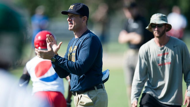 Michigan football coach Jim Harbaugh encourages participants during the Coach Jim Harbaugh's Elite Summer Football Camp, Friday, June 5, 2015, at Prattville High School in Prattville, Ala.