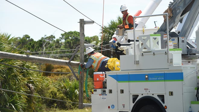 Pacific Gas and Electric Company workers from California hoist power lines Wednesday, Sept. 13, 2017, just south of the Hobe Sound National Wildlife Refuge off of U.S. Highway One in Hobe Sound.