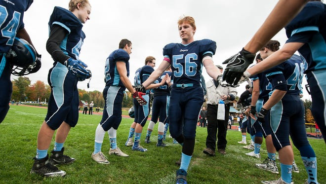 MMU senior Adam Fischer (56) in honored by the team before the start of the gamed during senior day at the high school football game between the Hartford Hurricanes and the Mount Mansfield Cougars at MMU High School on Saturday afternoon October 14, 2017 in Jericho.