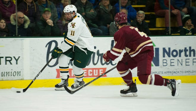 Vermont forward Conor O'Neil (11) skates past Eagles defenseman Michael Kim (4) with the puck during the men's hockey game between the Boston College Eagles and the Vermont Catamounts at Gutterson Field House on Friday night November 10, 2017 in Burlington.