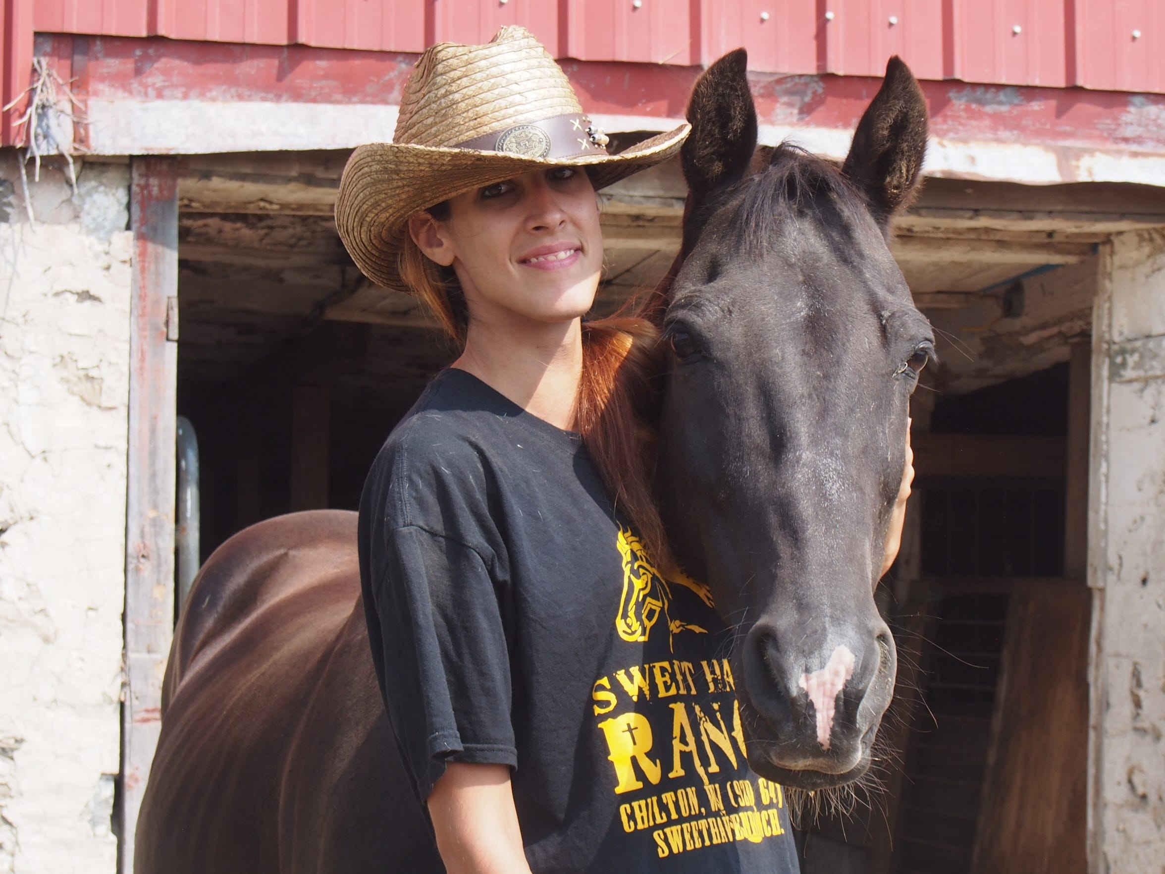 Desiree Doty poses with Shadow, a horse which she adopted and stables at the ranch.