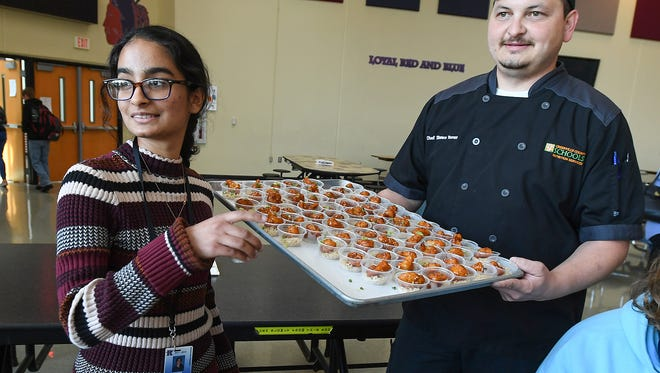 Riverside sophomore Nayha Hussain, left, who was the 2017 Healthy Lunchtime Throwdown winner, tells fellow classmate Kayla Murray about her winning dish, Gobi Manchurian, during lunch at Riverside on Tuesday, April 10, 2018.