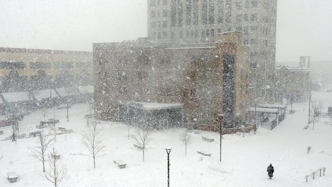 A lone pedestrian walks through blowing snow at Houdini Plaza during a snowstorm Tuesday, February 2, 2016, in Appleton, Wisconsin.