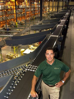 Gene Forte of Forte Industries at the Totes Isotoner distribution facility in West Chester, with the conveyor equipment his company designed. Forte Industries was recently bought by the Swiss company Swisslog.