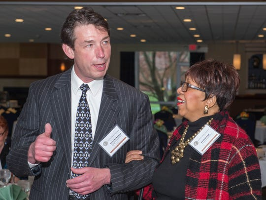 Battle Creek Enquirer Executive Editor Michael McCullough escorts George Award winner and the late Dorothy Height to her table in 2016.