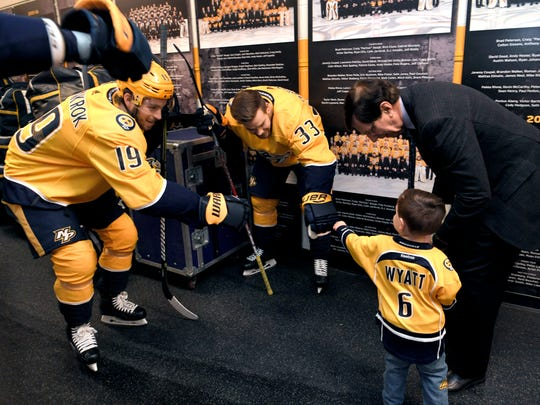 Predators' players Calle Jarnkrok (#19) and Viktor Arvidsson (#33) give Wyatt Poile a fist pump outside the locker room before a game at Bridgestone Arena on Feb. 25, 2018. General Manager David Poile, left, spends time with his grandson, Wyatt, before a game at Bridgestone Arena on Feb. 25, 2018.