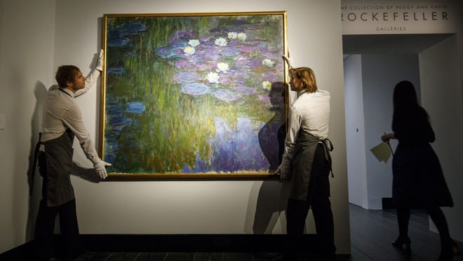 Gallery assistants pose with the painting 'Nympheas en fleur' by French artist Claude Monet during a photocall at Christie's auction house in London, Britain, Feb. 20, 2018.