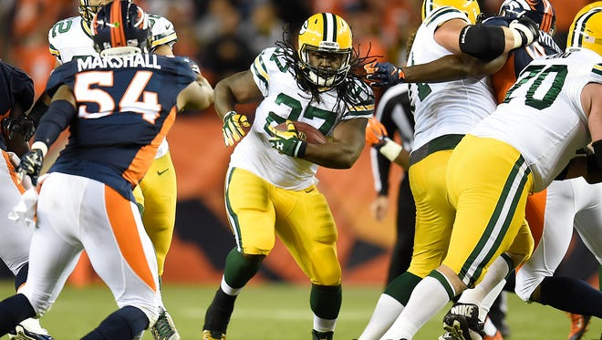 Green Bay Packers running back Eddie Lacy (27) runs into the line against the Denver Broncos during Sunday night's game at Sports Authority Field in Denver, Colo.