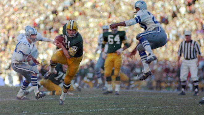 Green Bay Packers Jim Taylor runs with a pass against the Dallas Cowboys. Taylor, born in Baton Rouge and an LSU product, played 10 NFL seasons.