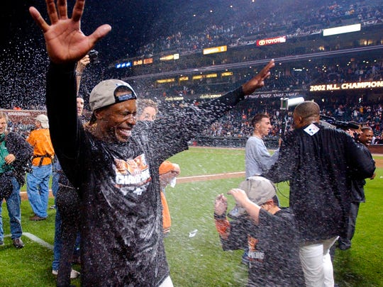 San Francisco Giants' Kenny Lofton celebrates on the field after the Giants defeated the St. Louis Cardinals in Game 5 of the NLCS in San Francisco, Monday, Oct. 14, 2002.