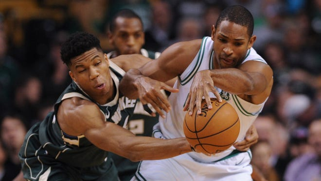 Bucks forward Giannis Antetokounmpo  tries to knock the ball away from Celtics forward Al Horford during the first half Monday night at TD Garden in Boston.