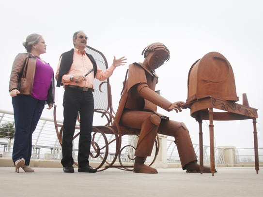 """Barbara Bengochea-Perez works as a translator for Colombian artist Edgardo Carmona as he speaks about a piece titled, """"Sintonia"""" that depicts the """"nostalgia of passing time,"""" which is part of a public display of work in downtown Fort Myers."""