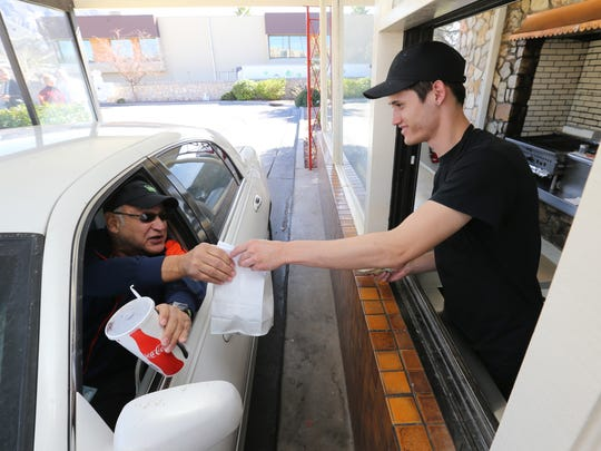 Ruben Schaeffer gets his food order in early January from then-Charcoaler Drive-In manager Sean Chacon.