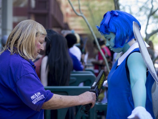Security checks a convention-goer at Phoenix Comicon