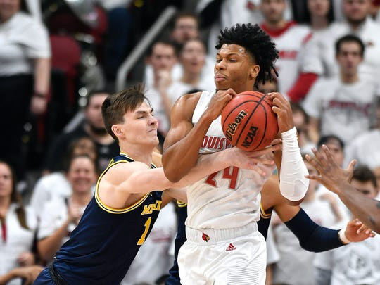 Michigan center Jon Teske (15) attempts to strip the ball away from Louisville forward Dwayne Sutton (24) during the first half of an NCAA college basketball game in Louisville, Ky., Tuesday, Dec. 3, 2019. (AP Photo/Timothy D. Easley)