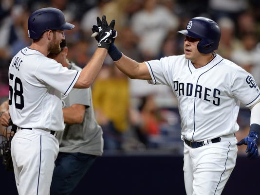 San Diego Padres Christian Villanueva is congratulated by Rocky Gale at home plate after hitting a home run during the fifth inning of a baseball game against the Arizona Diamondbacks Wednesday, Sept. 20, 2017, in San Diego. (AP Photo/Orlando Ramirez)