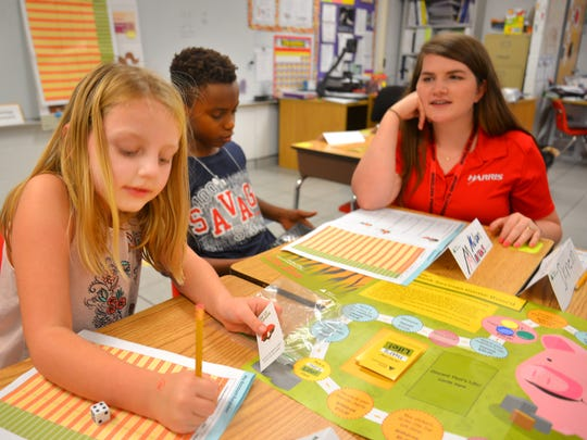 Harris Corp. financial analyst Vicki Baker (right) works with third graders Mariah Leavey and Marcus Nelson. Harris Corp. workers were at Palm Bay Elementary school on Dec. 8, 2017, for Junior Achievement Day. Harris employees were teaching classes about business and finance as part of the Junior Achievement curriculum.